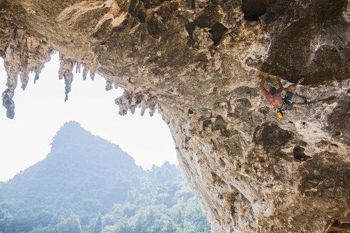 Rock climber on Odins Dan cave, Yangshuo, Guangxi Zhuang, China - CUF31592