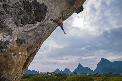 Scenic low angle view of rock climber hanging from arch of spicy noodle 5.14c, White Mountain, Yangshuo, Guangxi Zhuang, China - CUF31598