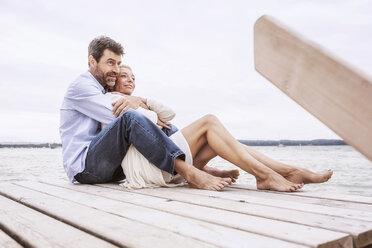 Mature couple sitting, hugging, on pier - CUF31610