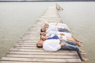 Group of friends lying in a row, on pier - CUF31625