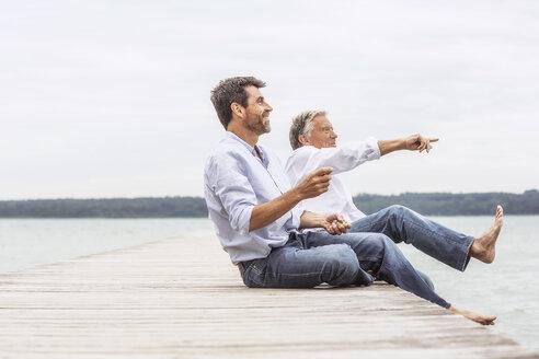 Two men sitting on pier, throwing stones, smiling - CUF31631