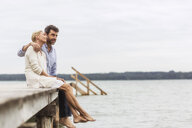 Mature couple sitting on edge of pier, relaxing - CUF31634