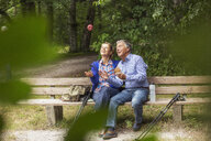 Couple sitting on bench in forest, woman throwing apple in air - CUF31640