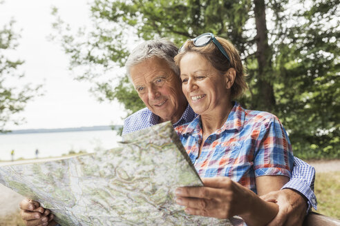 Couple in forest, looking at map, smiling - CUF31646