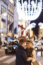 Romantic young couple on New Bond street at xmas, London, UK - CUF31769