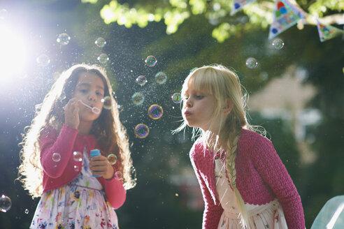 Two girls blowing bubbles in sunlit garden - CUF31811