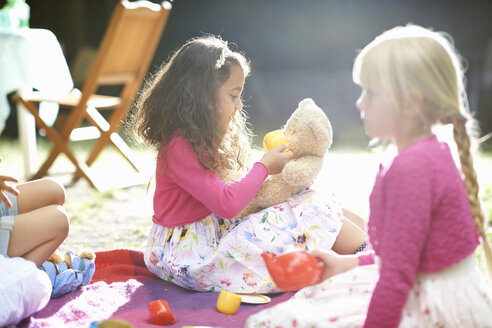 Girls playing picnics at garden birthday party - CUF31814