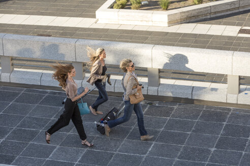 Three adult women running across elevated walkway - ISF09735