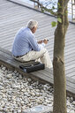 High angle view of senior businessman texting on smartphone on hotel terrace - ISF09789