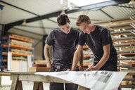 Two young male carpenters working on blueprint in workshop - CUF32068