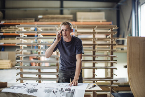 Young male carpenter talking on smartphone in workshop - CUF32071