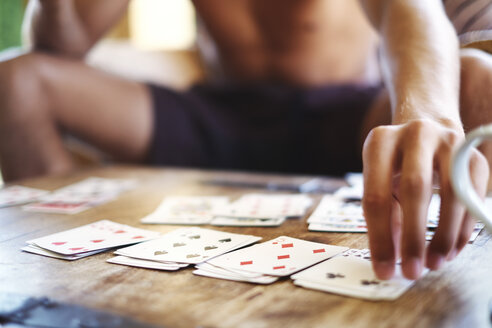 Cropped shot of young man  playing cards at table - CUF32158