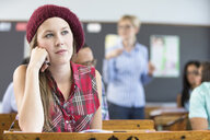 Female student, sitting at desk in classroom, thinking - CUF32275
