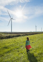 Mature woman standing in field, watching wind turbines on windfarm, rear view, Rilland, Zeeland, Netherlands - CUF32380