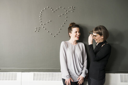 Two women by wall with heart shape - ISF09840