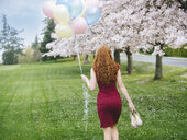 Rear view of young woman with long wavy red hair and bunch of balloons strolling in spring park - ISF09846