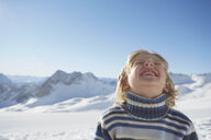Portrait of young boy in snowy landscape, looking up, smiling - ISF09885
