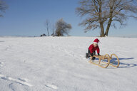 Young boy pushing sled down hill - ISF10014
