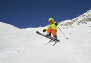 Young boy skiing down mountain, low angle view - ISF10026