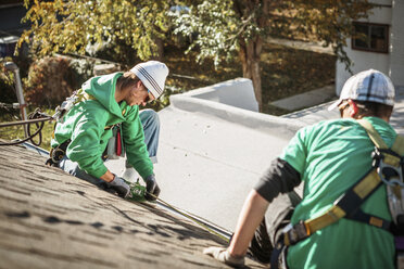 Solar panel installation crew members on roof of house - ISF10221