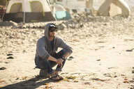 Man at beach camp, Malibu, California, USA - ISF10287