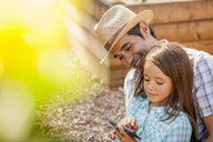 Girl on fathers lap using smartphone in community garden - ISF10305