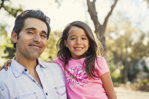 Portrait of mid adult man and daughter in community garden - ISF10323
