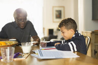 Grandfather at table with grandson doing homework - CAIF20703
