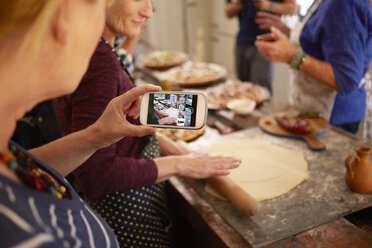Woman with camera phone photographing friend making pizza dough in cooking class - CAIF20718