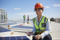 Portrait smiling, confident female engineer with digital tablet inspecting solar panels at sunny power plant - CAIF20754
