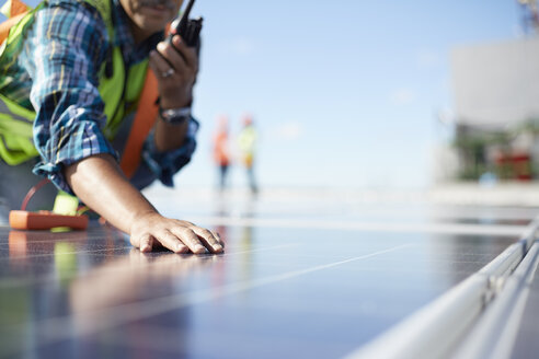 Engineer with walkie-talkie inspecting solar panels at power plant - CAIF20757