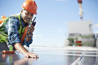 Engineer with walkie-talkie inspecting solar panel at power plant - CAIF20760