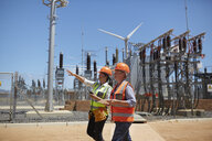 Female engineers with digital tablet at sunny power plant - CAIF20766