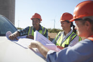 Engineers reviewing blueprints on truck at sunny wind turbine power plant - CAIF20769