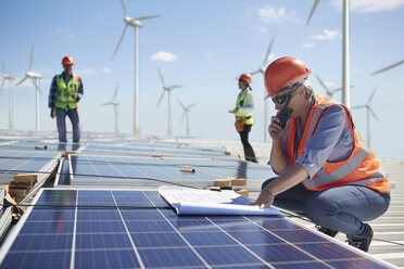 Engineer with walkie-talkie and blueprint at solar panel at sunny power plant - CAIF20772