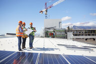 Engineers with blueprint at solar panels at sunny power plant - CAIF20775