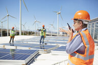 Female engineer using walkie-talkie at alternative energy power plant - CAIF20778