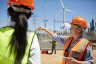 Female engineer with digital tablet talking to colleague at wind turbine power plant - CAIF20781