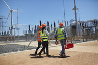 Engineers with toolbox walking at sunny wind turbine power plant - CAIF20784