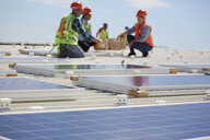 Engineers installing solar panels at sunny power plant - CAIF20787