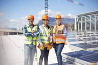 Portrait confident, smiling engineers at sunny solar power plant - CAIF20790
