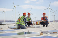 Engineers installing solar panels at alternative energy power plant - CAIF20793
