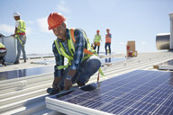 Engineer installing solar panels at sunny power plant - CAIF20796