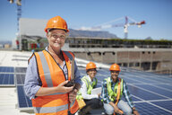 Portrait smiling, confident female engineer with walkie-talkie at sunny solar power plant - CAIF20799