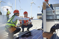 Female engineers talking, examining solar panels at power plant - CAIF20802