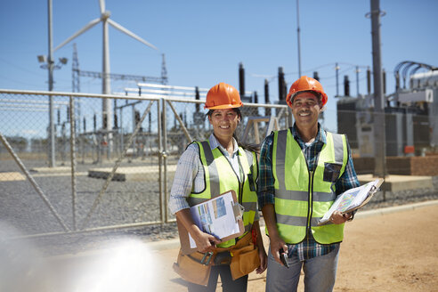 Portrait smiling, confident engineers with clipboards at power plant - CAIF20811