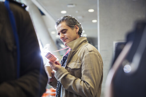Businessman looking at conference identification pass - CAIF20817