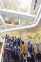 Business people descending stairs in modern lobby atrium - CAIF20850