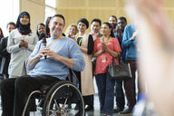 Audience clapping for male speaker in wheelchair - CAIF20898