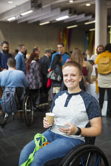 Portrait smiling, confident young woman in wheelchair drinking coffee at conference - CAIF20910